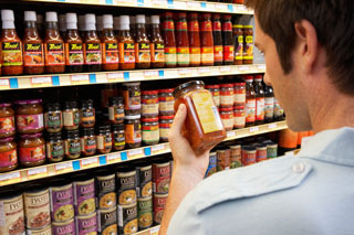 Image of man reading a food label at a supermarket to illustrate the importance of reading labels.