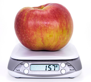 an image of an apple sitting on food scales to illustrate calculating daily energy needs.